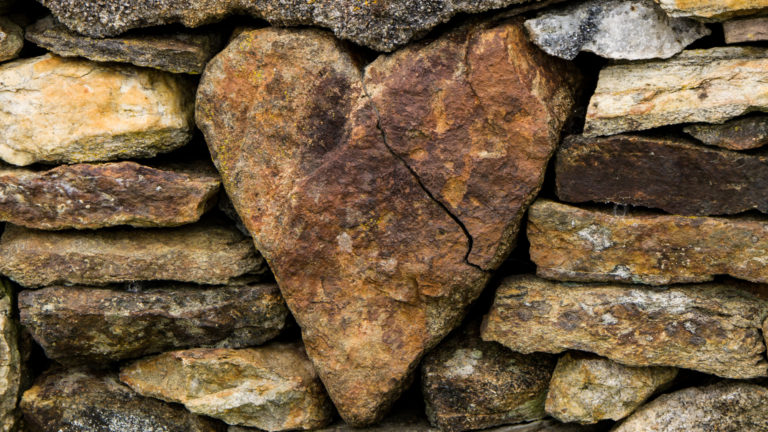 Biblical heart of a pastor - A rock in a heart shape surrounded by many other rocks.