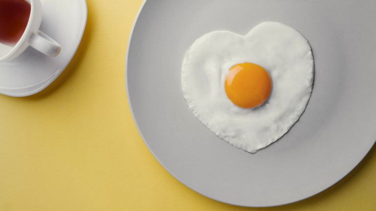 Shaped by grace - a fried egg in the shame of a heart on a plain plate