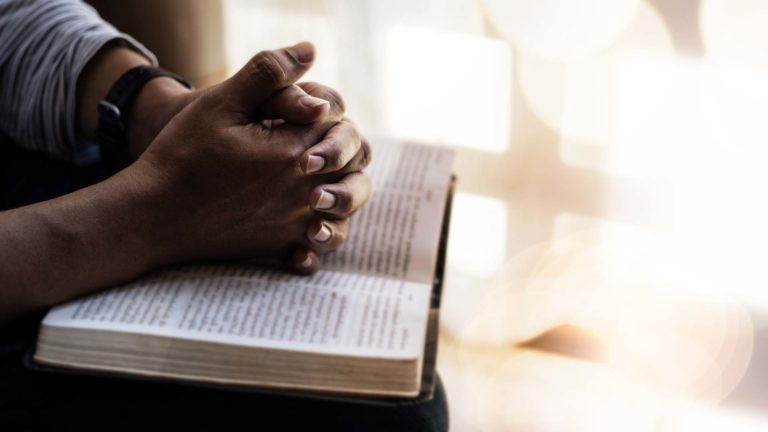 Purpose of Apologetics - Bible open on a person's lap with praying hands on it.