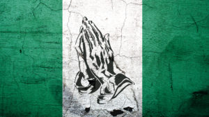 Conflict in Nigeria - Nigerian flag with praying hands on it.