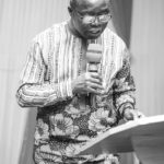 Preaching and Teaching the truth - Man standing by the pulpit reading the bible.