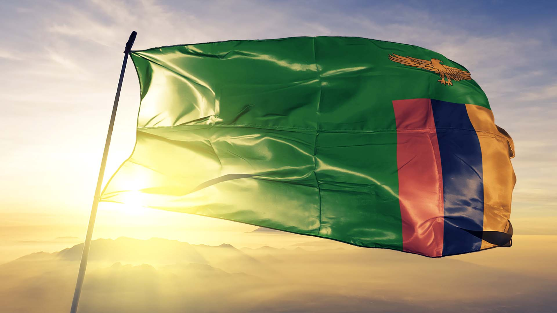 Patriotism - Zambian flag blowing in the wind, with sun golden glow shinning behind flag.