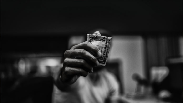 Corruption - A man with a dollar bill in his hand.
