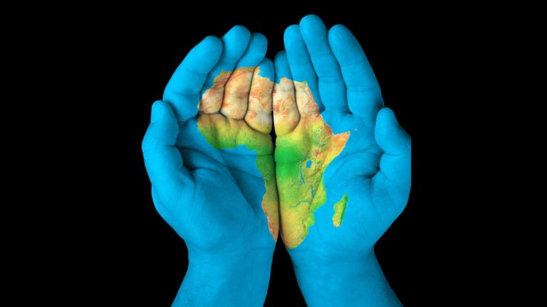 Reforming Africa - Hands painted blue with African map painted on it.