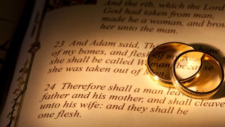 Biblical Marriage - Two rings on top of the a page in the bible in the book of Genesis