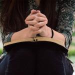 Mulher sentada em espaço aberto, provavelmente um parque com vegetação, orando com as mãos entrelaçadas sobre a Bíblia